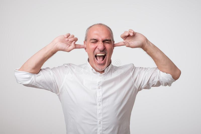 Mature european man closing his ears because of loud sound and noise. I do not want listen to you. royalty free stock photos