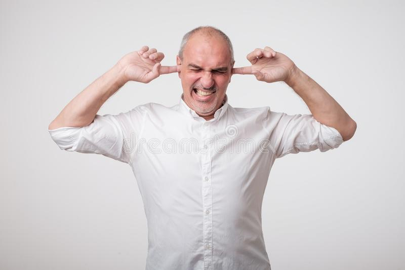 Mature european man closing his ears because of loud sound and noise. I do not want listen to you. stock photos
