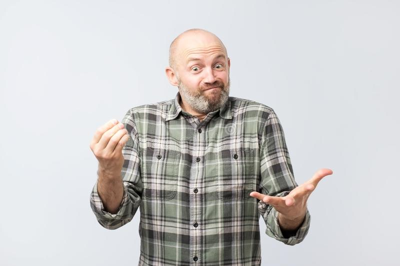 Mature european man explaining something simple being questioned someone, frowning and grimacing royalty free stock photo