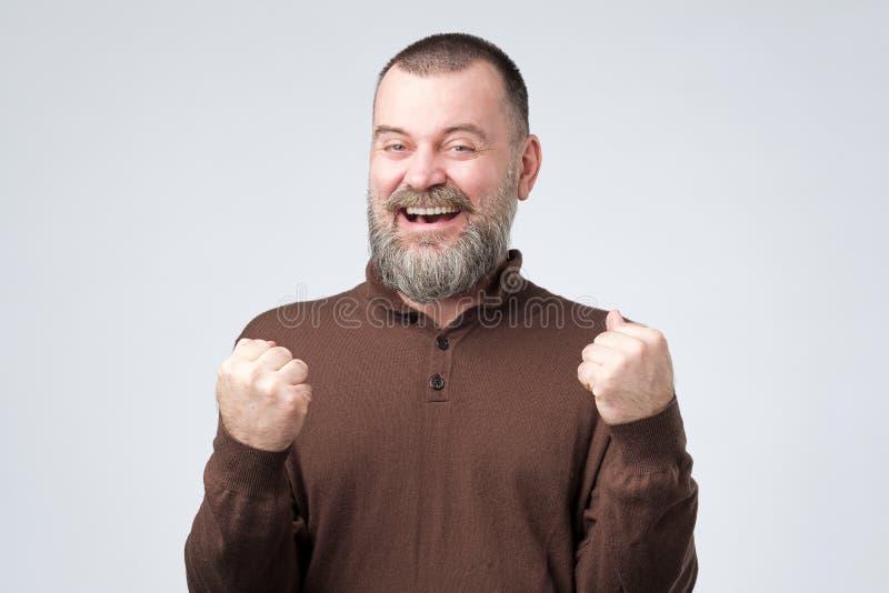 Mature european man raising fists up celebrating his success. stock photo