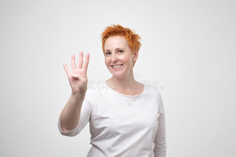 Mature european woman with red hair dressed in white t-shirt showing four fingers stock photos