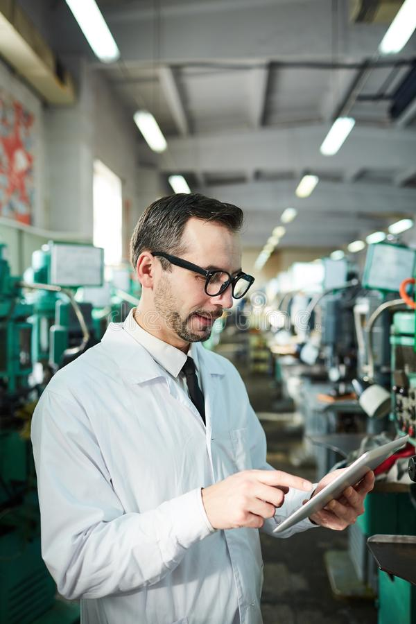 Mature Factory Worker Holding Tablet royalty free stock images