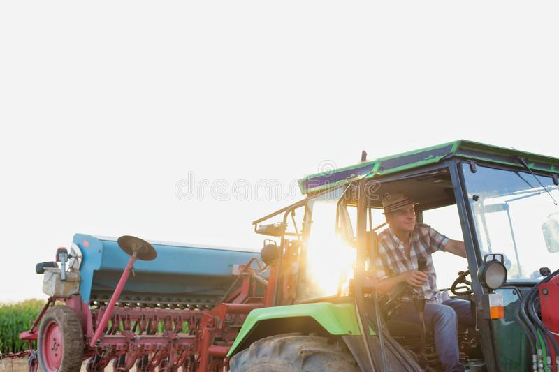 Mature farmer driving tractor in field with lens flare in background. Photo of Mature farmer driving tractor in field with lens flare in background stock photo