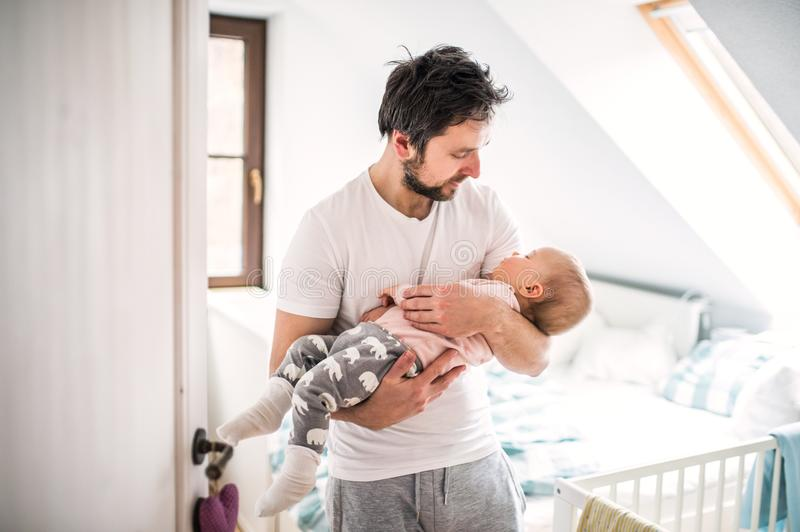 Father carrying a sleeping toddler girl in bedroom at home. stock images