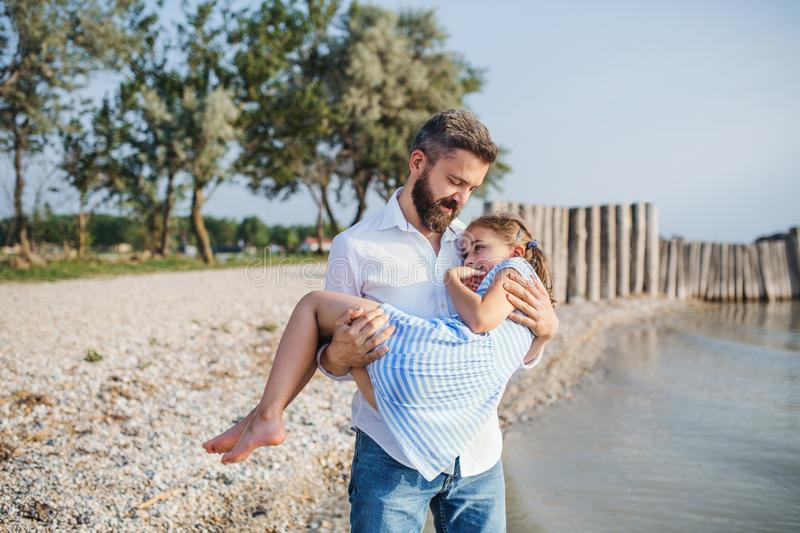 Mature father carrying small daughter on a holiday by the lake, walking. royalty free stock photos