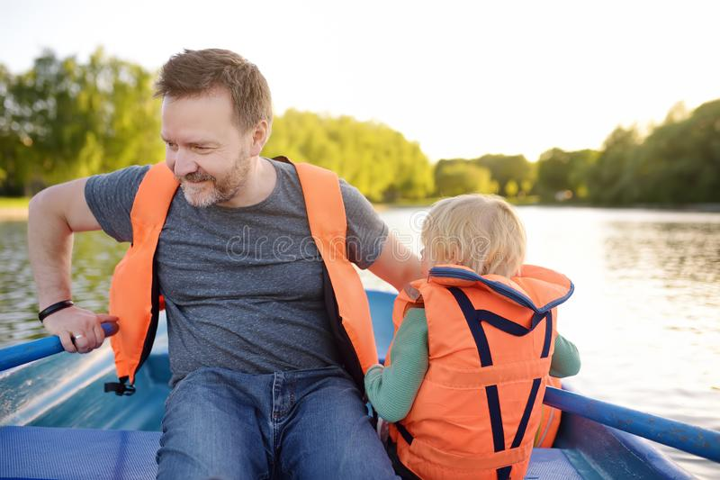 Mature father and little son boating on a river or pond at sunny summer day. Quality family time together on nature royalty free stock image