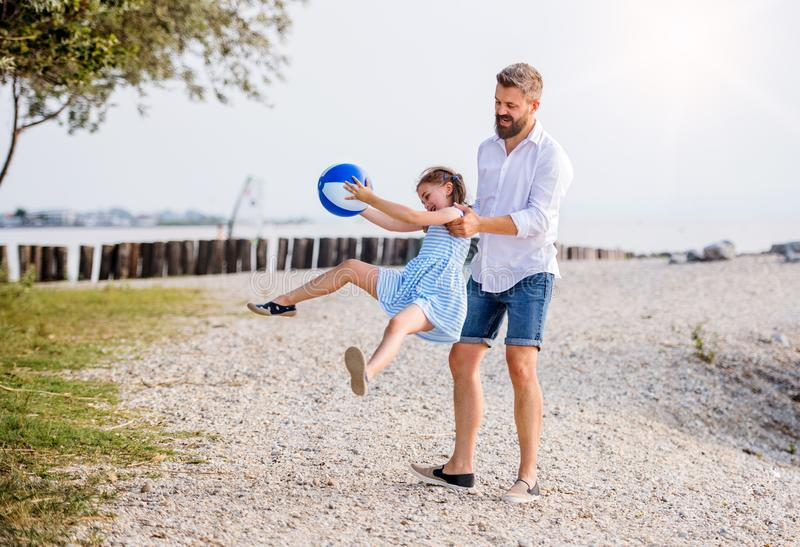 Mature father and small daughter on a holiday playing by the lake. royalty free stock photo