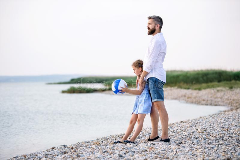 Mature father and small daughter on a holiday playing by the lake. stock image