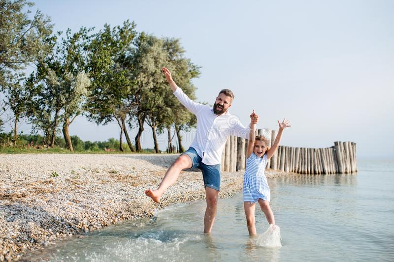 Mature father and small daughter on a holiday playing by the lake. stock images