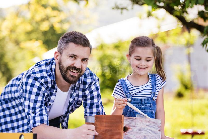 Father with a small daughter outside, painting wooden birdhouse. stock images