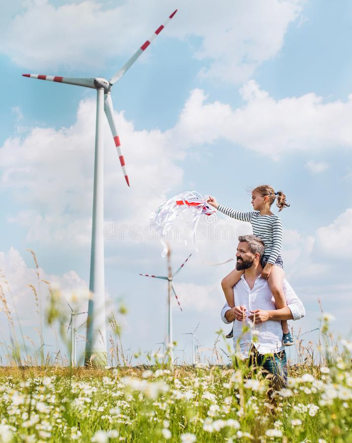 Mature father with small daughter walking on field on wind farm. stock image