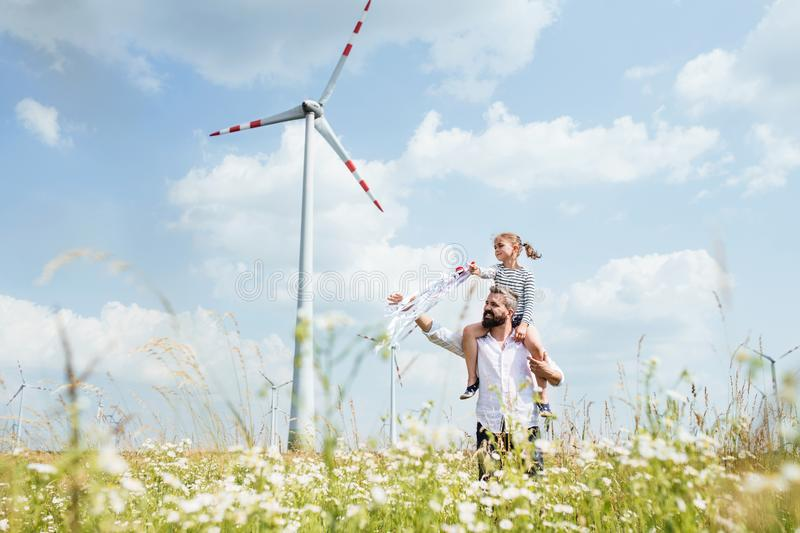 Mature father with small daughter walking on field on wind farm. royalty free stock photos
