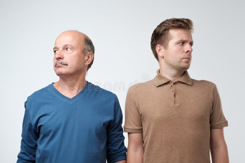 Mature father and son being in quarrel looking aside royalty free stock image
