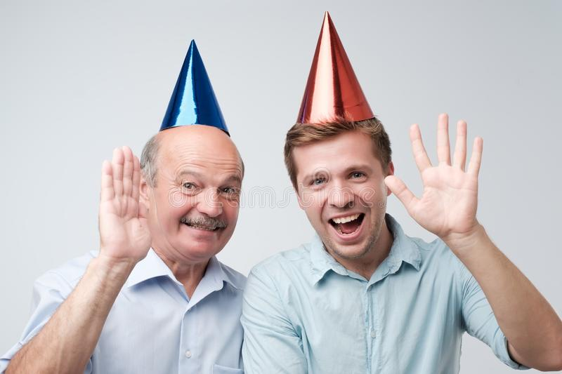 Father and son celebrating birthday or other family holiday. They are happy to see their guests stock photo