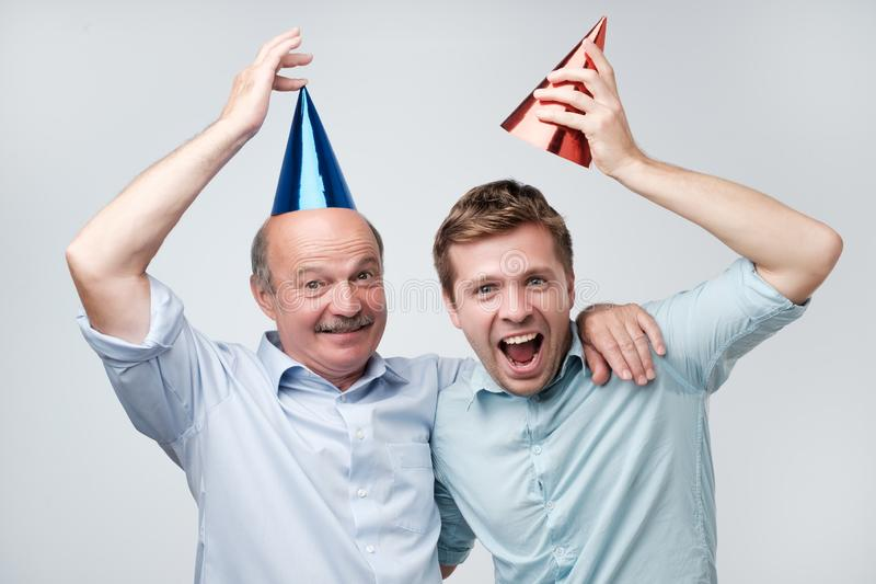 Father and son celebrating birthday or other family holiday. They are happy to see their guests. Mature father and son celebrating birthday or other family stock photo