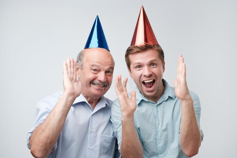 Father and son celebrating birthday or other family holiday. They are happy to see their guests. Mature father and son celebrating birthday or other family royalty free stock photo