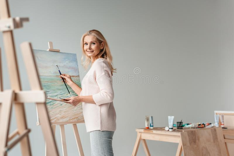 mature female artist smiling at camera while painting on easel stock photo