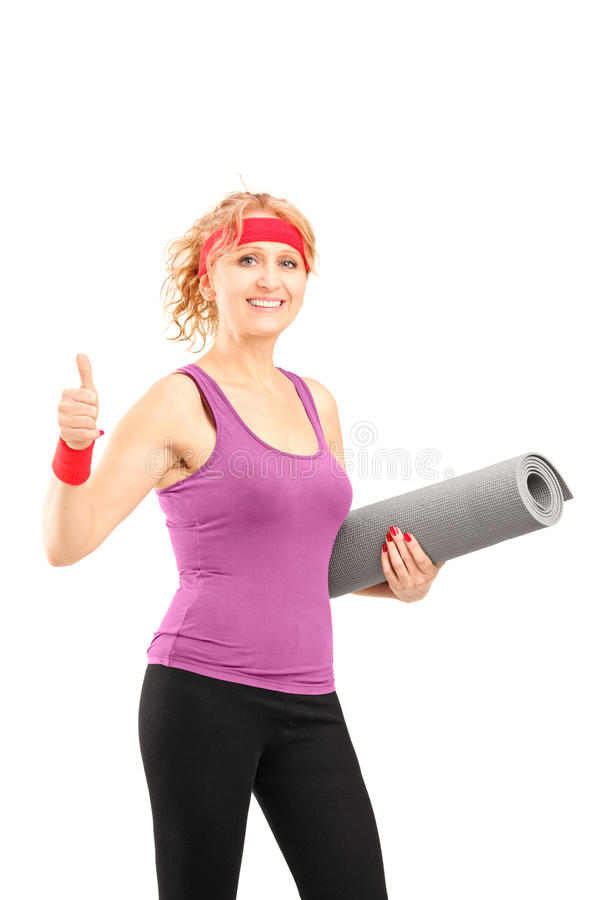 Download A Mature Female Athlete Holding A Mat And Giving A Thumb Up Stock Photography - Image: 29113232