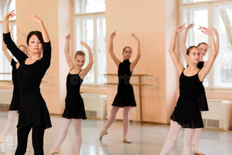 Mature female ballet instructor demonstrating ballet moves to a group of teenage girls stock image
