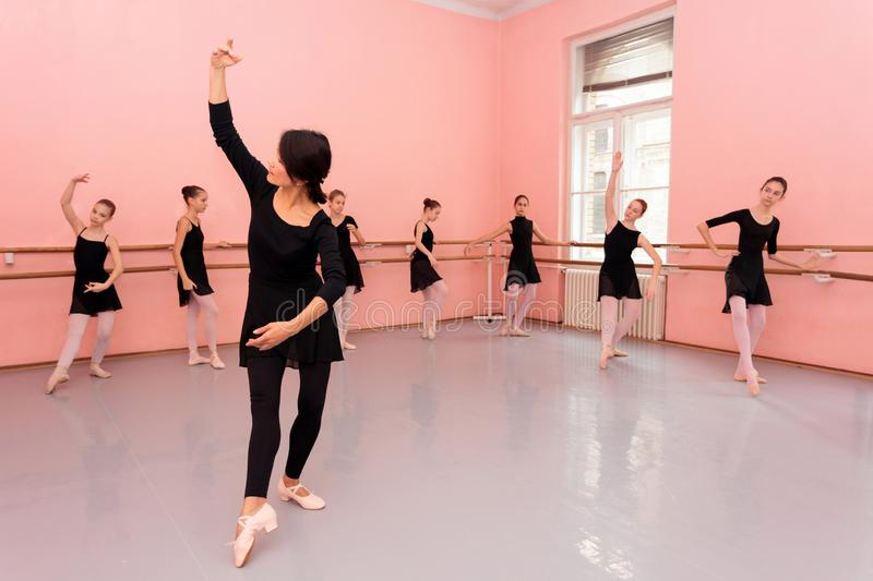 Mature female ballet teacher demonstrating dancing moves in front of a group of young teenage girls stock photos