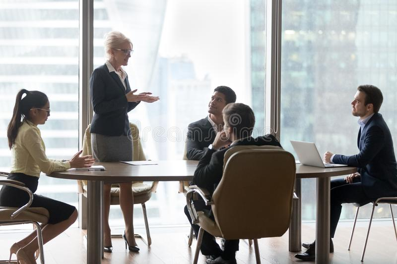 Mature female manager speaking to executive team at group meeting stock photos