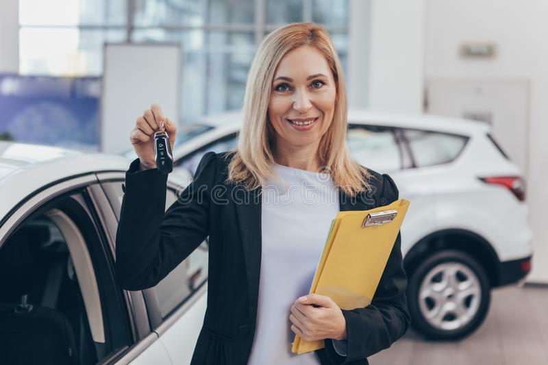 Saleswoman working at car dealership. Mature female car dealer smiling to the camera cheerfully, holding car keys, standing in front of a new automobile on sale royalty free stock photo