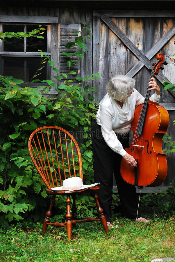 Mature female cellist. Mature female cellist with her instrument outdoors stock images