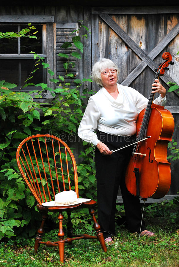 Mature female cellist. Mature female cellist with her instrument outdoors stock image