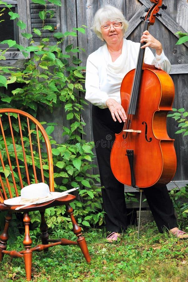Mature female cellist. Mature female cellist performing on her cello outside stock photos