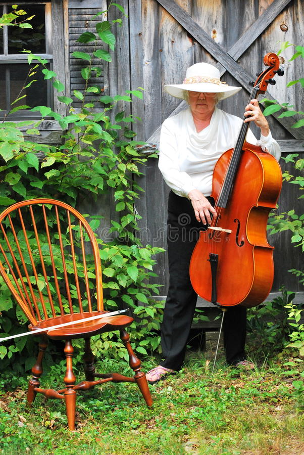Mature female cellist. Mature female cellist performing on her cello outside stock photography