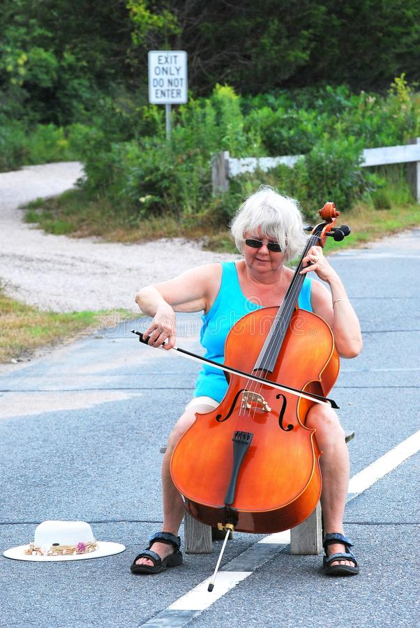 Female cellist performing. Mature female cellist performing a solo concert on the street outdoors stock image