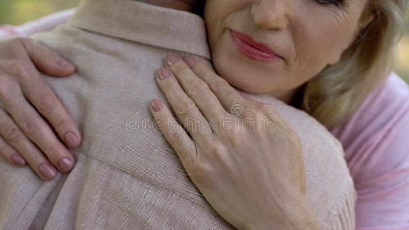 Mature female comforting man, wife supporting husband, bad news, togetherness stock photography