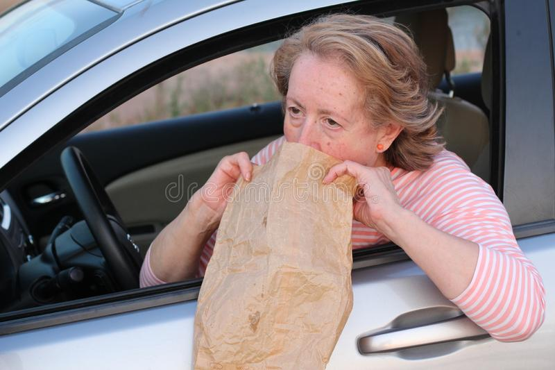 Mature female driver suffering from nausea y vomits royalty free stock image