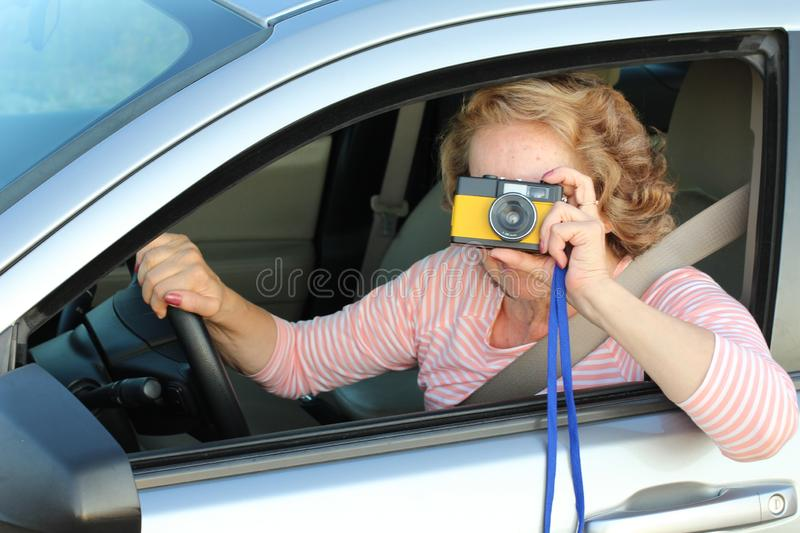 Mature female driver using vintage camera stock images