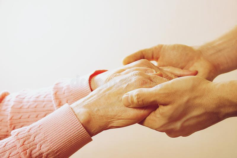 Mature female in elderly care facility gets help from hospital personnel nurse. Close up of aged wrinkled hands of senior woman. G. Male doctor care giver stock image