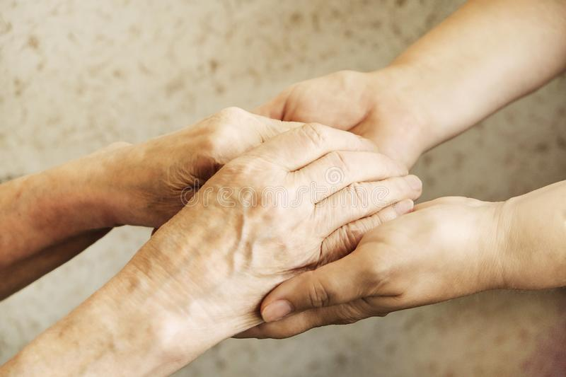 Close up of mature womans & nurse hands. Health care giving, nursing home. Parental love of grandmother. Old age related diseases. Mature female in elderly care royalty free stock image