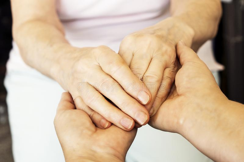 Close up of mature womans & nurse hands. Health care giving, nursing home. Parental love of grandmother. Old age related diseases. Mature female in elderly care stock photos