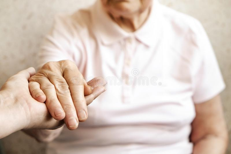 Close up of mature womans & nurse hands. Health care giving, nursing home. Parental love of grandmother. Old age related diseases. Mature female in elderly care stock image