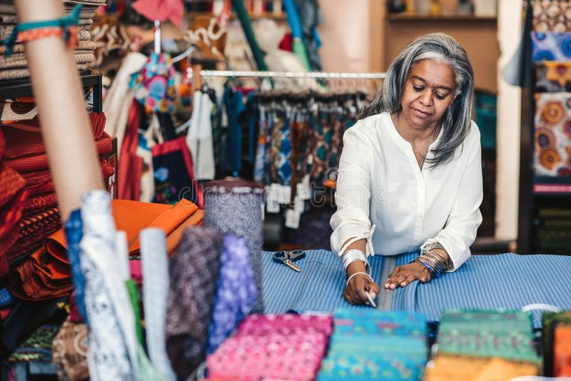 Mature woman marking cloth in her fabric shop before cutting stock images