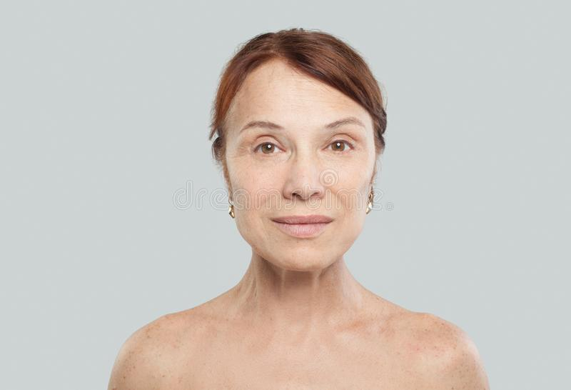 Mature female face on white background. Face lifting, cosmetology, aesthetic medicine and plastic surgery concept stock photography
