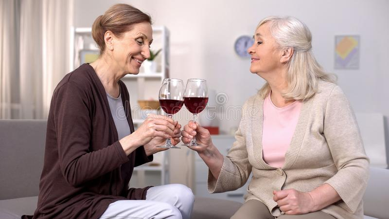 Mature female friends clinking red wine glasses enjoying peaceful rest at home stock images