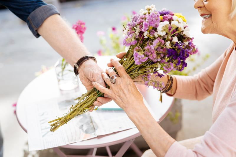 Mature female hands grabbing flowers stock photography