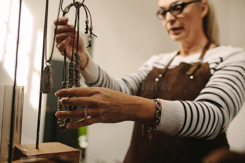 Mature female jeweler hanging a necklace on stand stock image