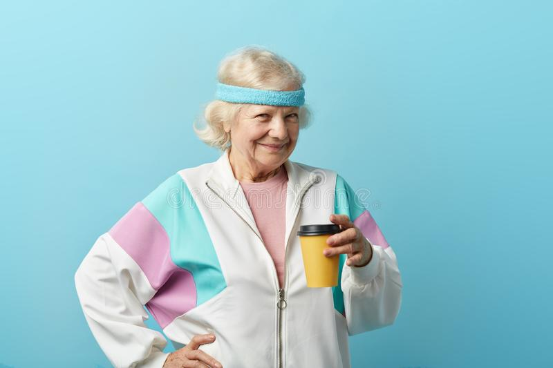 Mature female jogger in sports suit takes a rest after sport, with drink in hand. Mature female jogger in white sports suit taking a rest after morning running royalty free stock photography