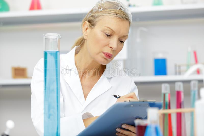 Mature female lab assistant doing scientific experiments in laboratory stock image