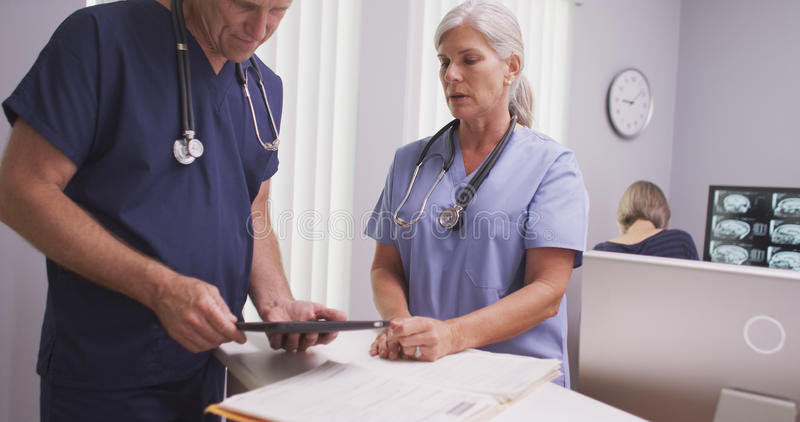 Mature female medical practitioner talking to male colleague at clinic desk royalty free stock photos