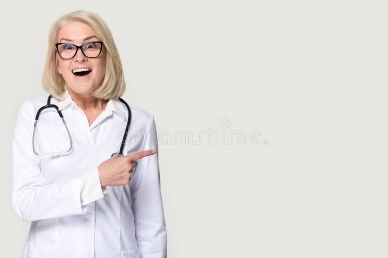 Mature female nurse point at blank copy space medical ad royalty free stock photos