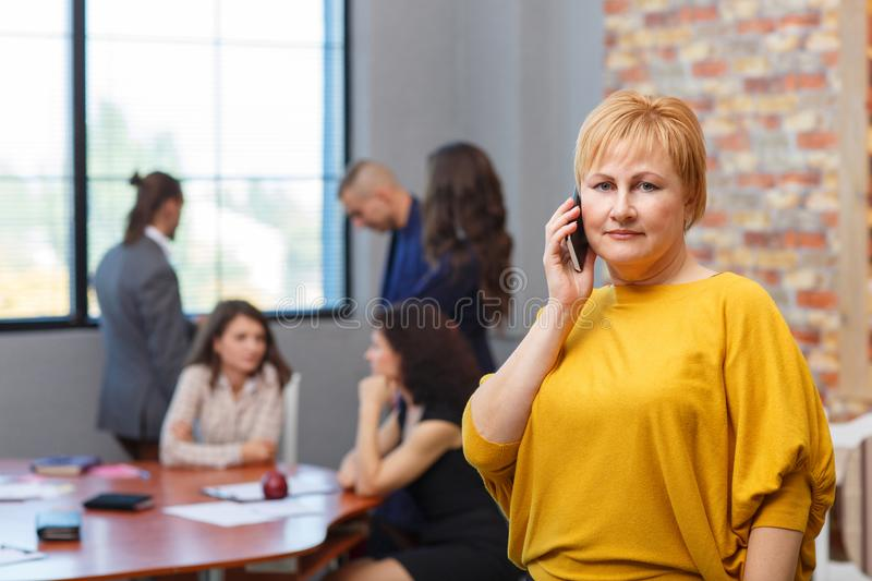 Mature female office worker talking on the phone. In the background, office workers. stock image