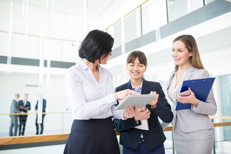 Female Professional Discussing Over Tablet Computer With Smiling royalty free stock photos