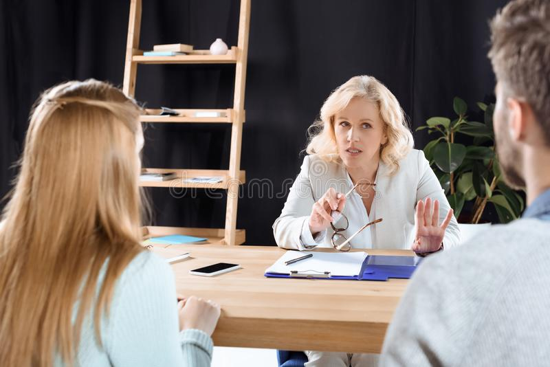 mature female psychotherapist talking with young couple royalty free stock photos